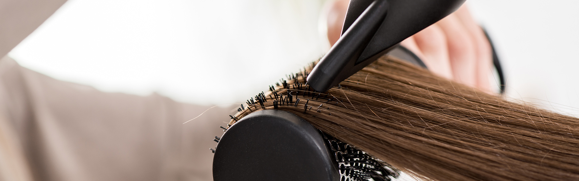 Close-up of a drying brown hair with hair dryer and round brush.