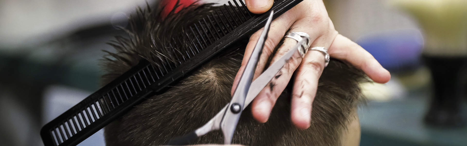Skilled female hairstylist is cutting cutting hair with scissors at a barber shop. Close up of by head and hands of hairdresser  with Scissors and comb.
